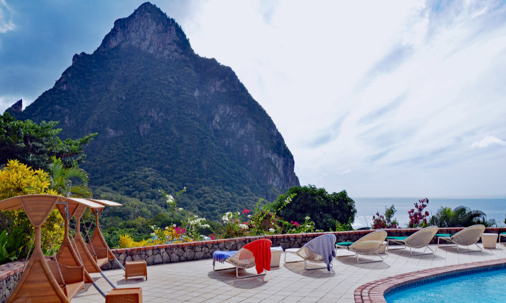 The Best Winter Getaways Where You Can Forget the Cold: Swimming pool, lounges with bright beach towels, and shaded swings on stone deck lined with tropical flowers overlooking St. Lucia island's Petit Piton and the Caribbean sea against a cloudy blue sky.