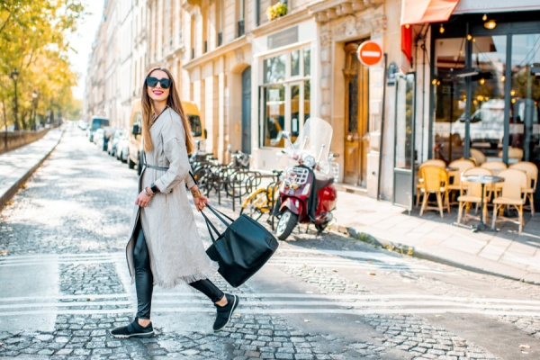 How to do Paris on a budget: Street view with traditional french cafe and woman walking during the morning in Paris