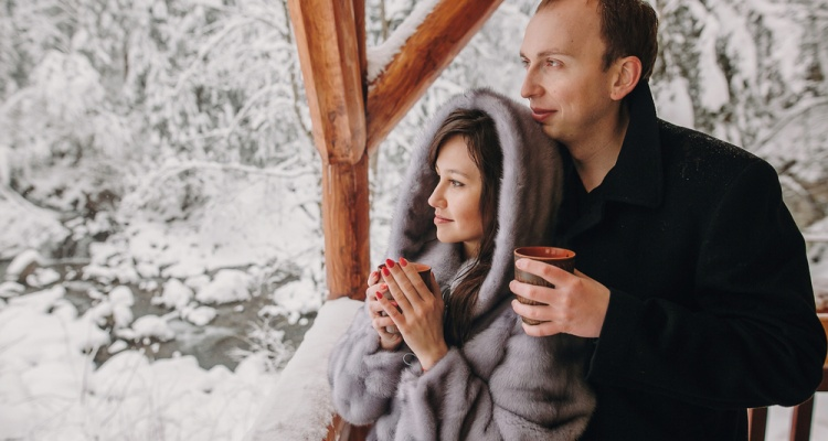 Stylish couple holding hot tea in cups and looking at winter snowy mountains from wooden porch