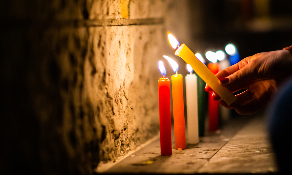 """things to do and places to visit in colombia: A woman's hand is seen, holding a lit candle to begin with the traditional day celebrated on December 7 called """"Noche de Velitas"""""""
