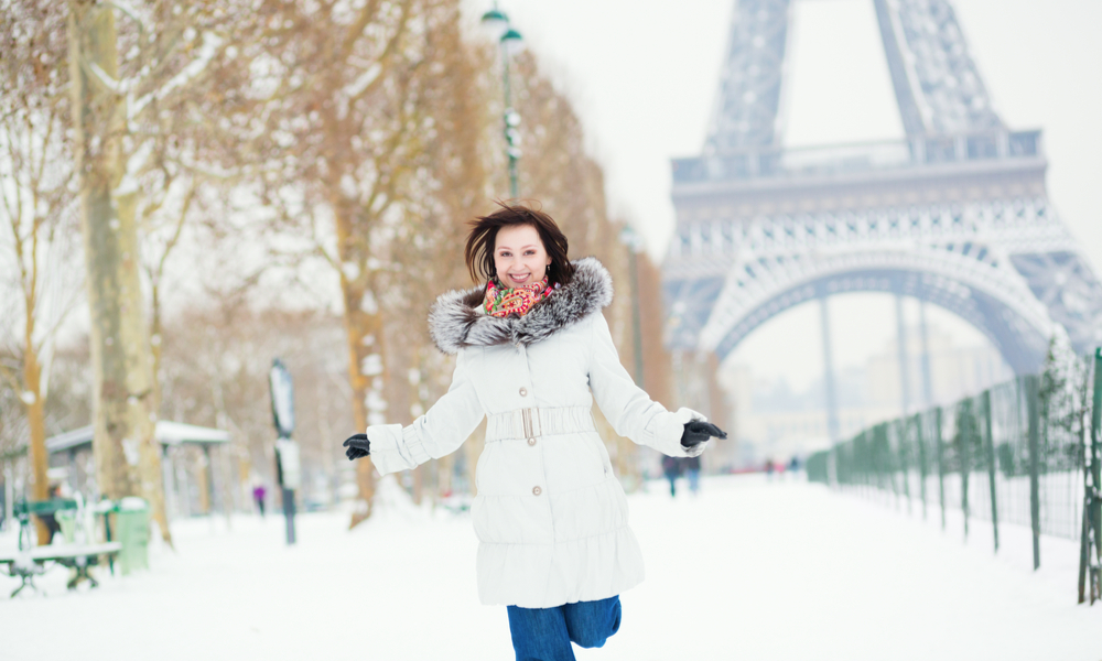 How to do paris on a budget: Girl happily jumping in Paris on a winter day