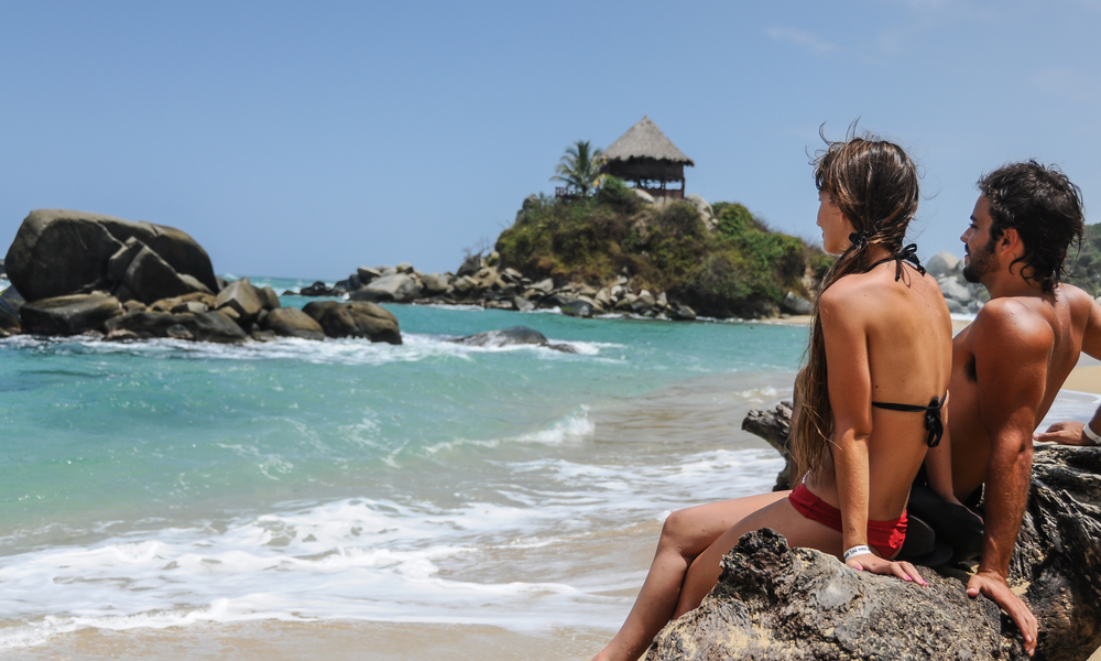 things to do and places to visit in colombia: Couple looking at the Sea, Tayrona National Park, Tropical Colombia. South America