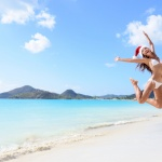 The Best Winter Getaways Where You Can Forget the Cold: girl jumping of joy and surprise on perfect white sand beach for winter holidays.