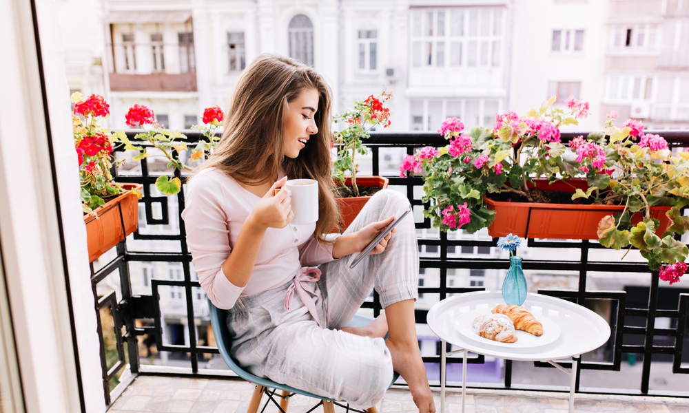 How to do Paris on a budget: girl with long hair in pajama having breakfast on balcony in the morning in city. She holds a cup, reading on tablet