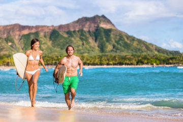 The Best Places to Surf in Hawaii in the Winter Season: Happy surf people having fun surfing on Waikiki beach, Honolulu, Oahu, Hawaii.