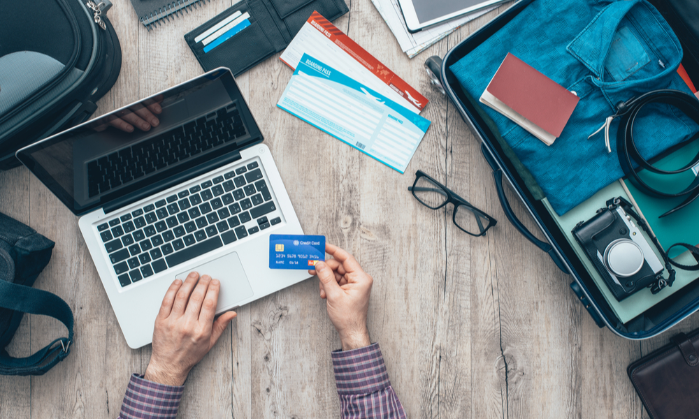 Everything You Need to Know About Open Jaw Flights: Traveler getting ready for a trip, he is packing his bag and booking a flight online using a credit card and a laptop