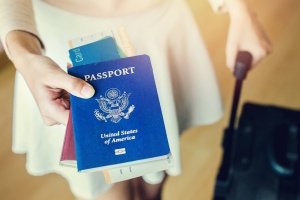 How to Avoid Common Visa Mistakes When Flying Internationally: Closeup of girl holding passports and boarding pass