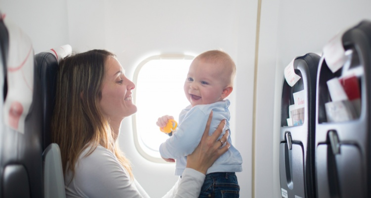 What you need to know when flying with a baby: Mother playing with her baby on flight