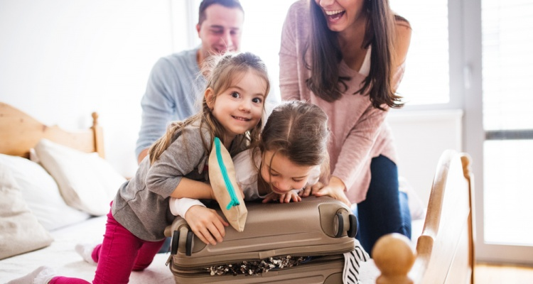 How to Save When You're Traveling with Kids: Young family with two children packing for holiday.