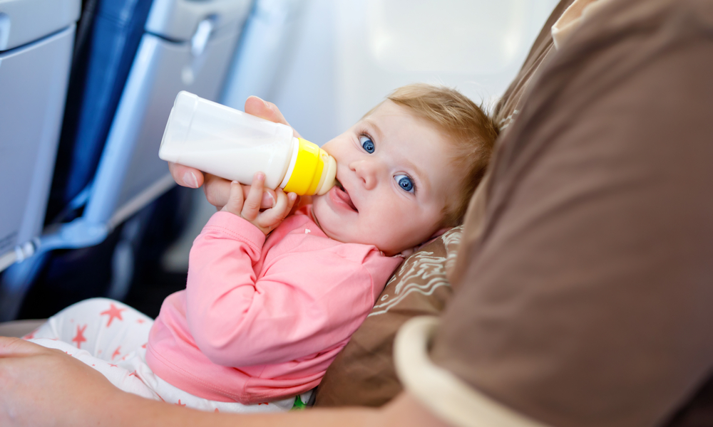 What you need to know when flying with a baby: Father holding baby daughter during flight on airplane