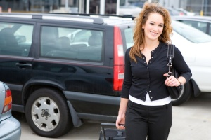 Tips for and alternatives to parking at the airport: Cheerful Woman Traveler in Parking Lot At Airport
