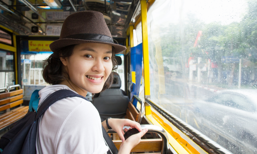 how to travel cheap: Young Asian woman in the bus with rainy day.