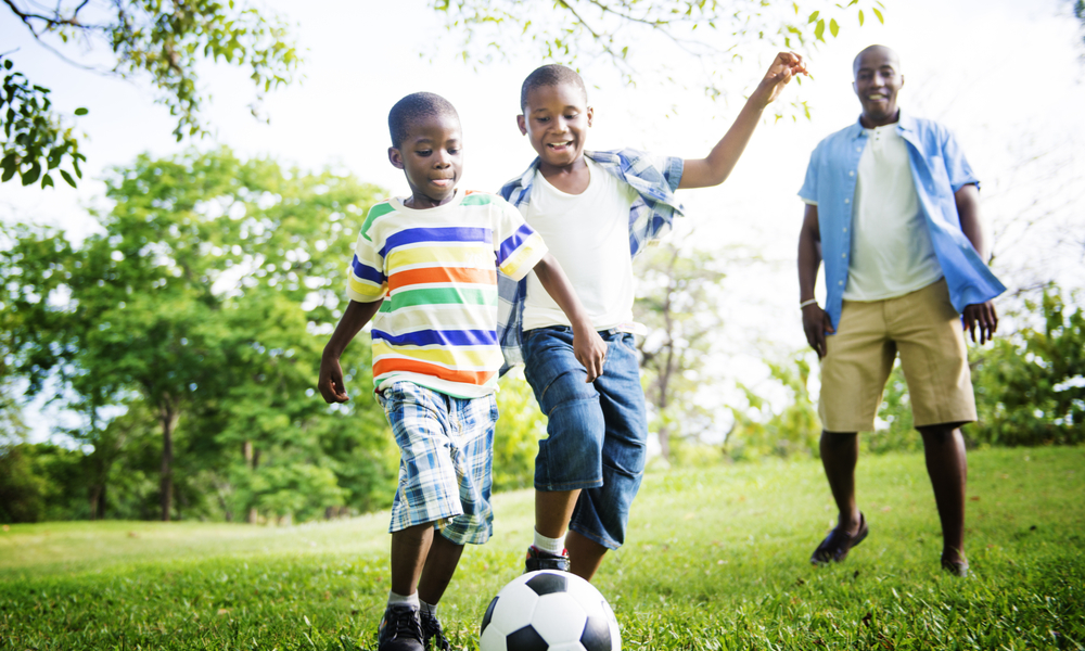 How to Save When You're Traveling with Kids: family plays soccer in park