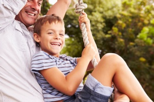 Best Free Things You Can Do in Denver with Kids: Father swinging with son at a playground