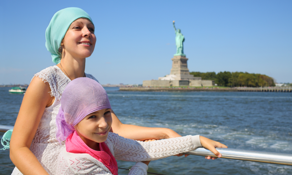 things to do in new york with kids:Portrait of mother with daughter on a boat in front of the famous Statue of Liberty in New York