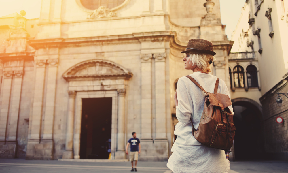 10 Tips for Flying Internationally on the Cheap: Back view of a young female wanderer out sightseeing in a foreign city during weekend overseas.