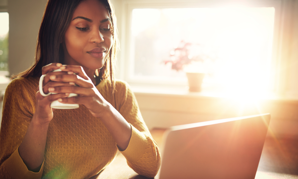 Tips for alternatives to parking at the airport: Adult woman smiling sitting near bright window while looking at open laptop computer on table and holding white mug