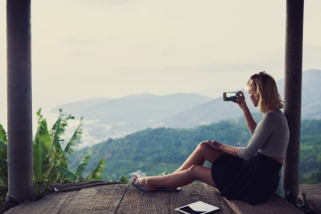How to take good instagram pictures on vcation: traveler woman taking a good picture of scenery while on holiday
