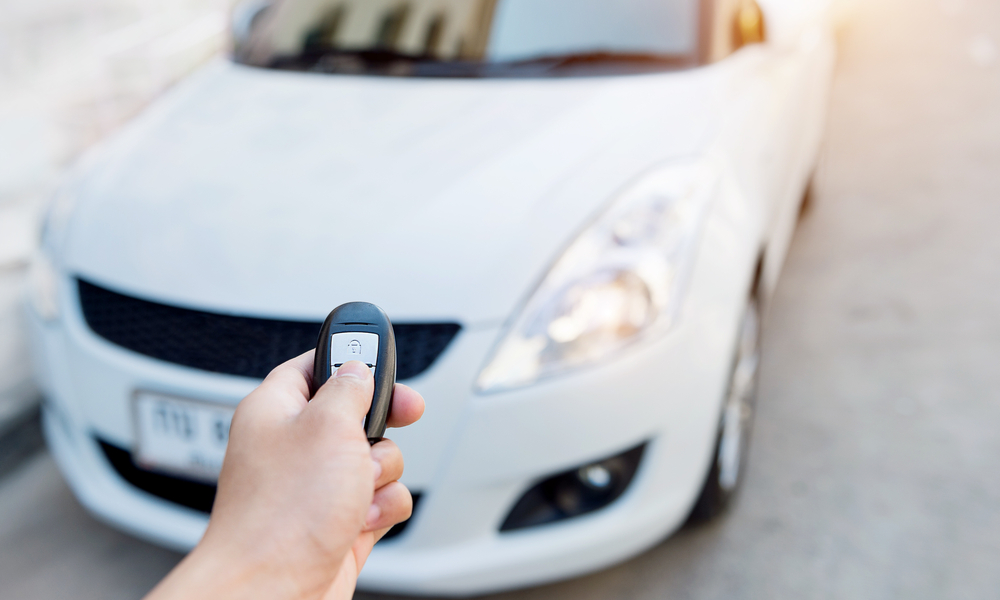 tips for and alternatives to parking at the airport: Hand holding car's remote control.