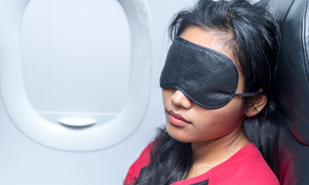 10 Tips for Flying Internationally on the Cheap: Portrait of a woman sleeping in an airplane.