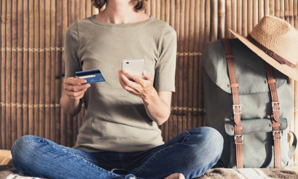 how to travel cheap: woman using credit card to book travel