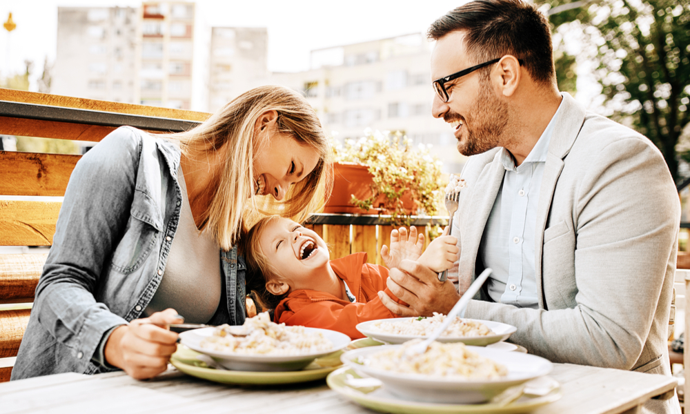 How to Save When You're Traveling with Kids: Happy family is enjoying pasta in restaurant.