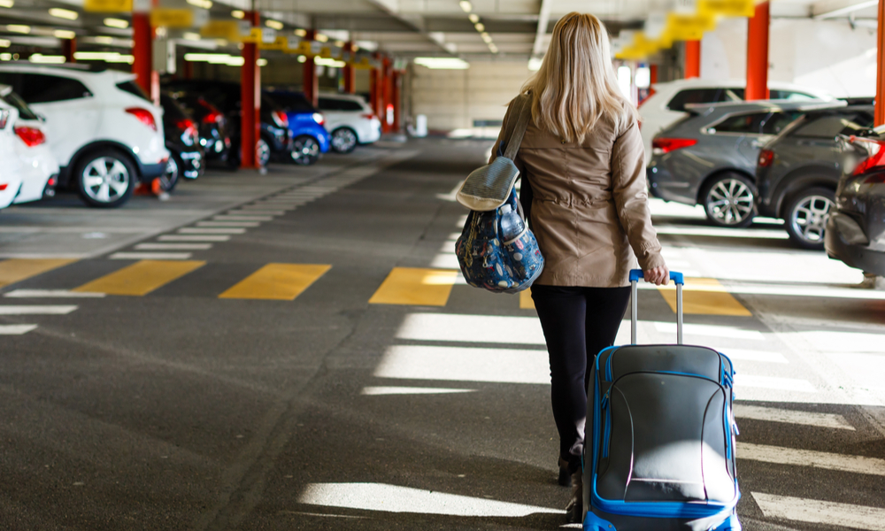 tips for and alternatives to parking at the airport: girl with bags at airport parking