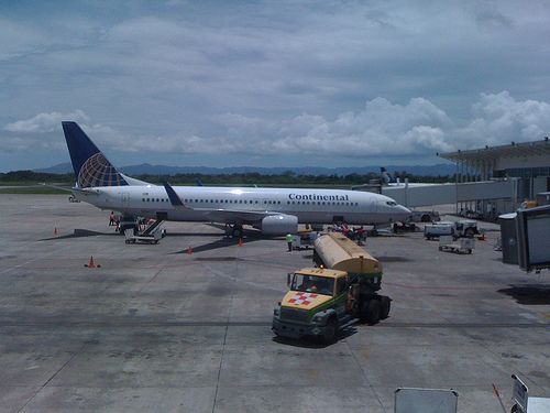 Continental Airlines plane parked at airport as bags are placed in it