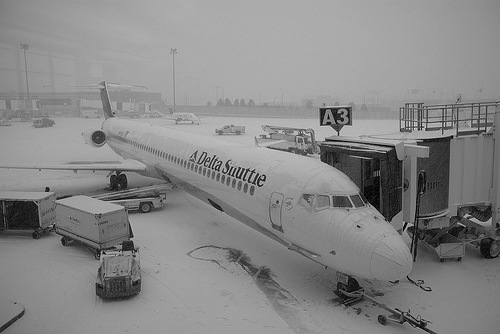 Delta Airlines plane sitting at a snowy Boston Logan Airport