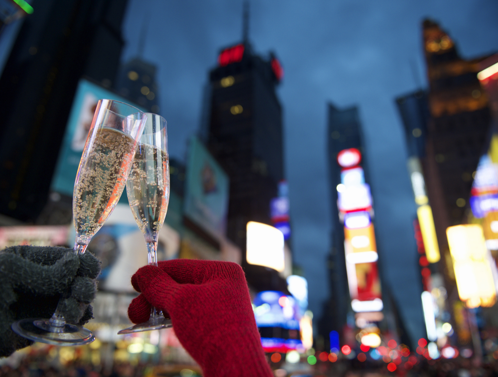 two glasses of champagne cheering at Times Square, NY