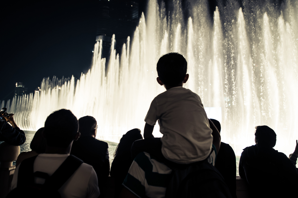 group of tourists watching fountain show
