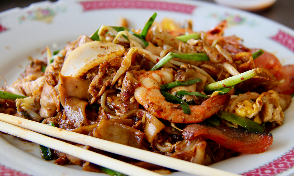 Char Kway Teow. Stir-fried rice noodles with seafood, fish cake, chinese sauce, beansprouts and chives; a highly popular street food dish in Singapore.