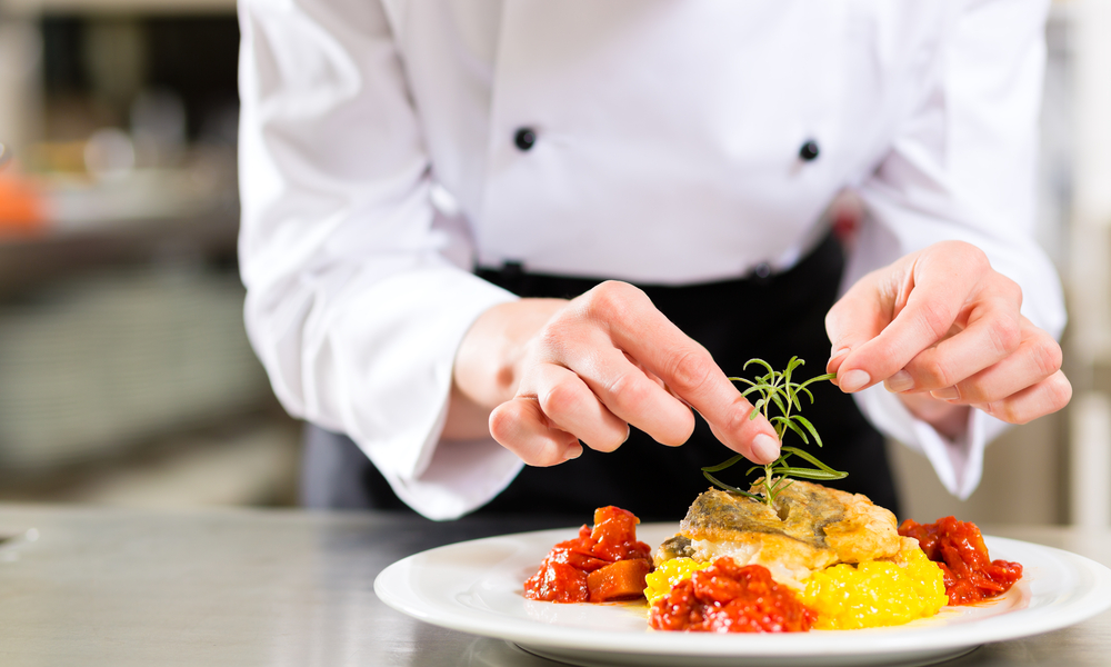 Female Chef in hotel or restaurant kitchen cooking, only hands, she is finishing a dish on plate