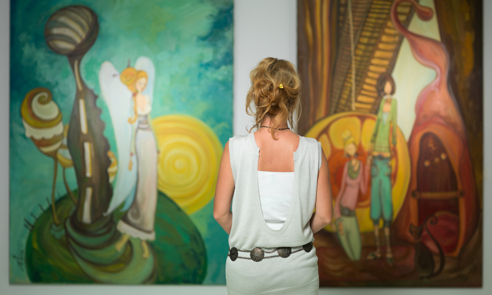 rear view of younga caucasian woman stading in an art gallery in front of two large colorful paintings
