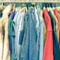 Vintage second hand clothes hanging on shop rack at weekly flea market