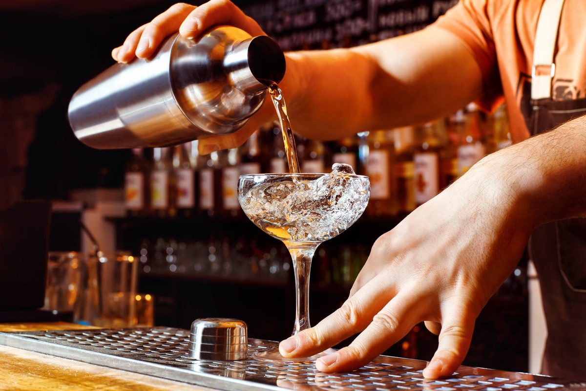 Male bartender is making cocktail pouring alcohol from shaker to glass at bar background.