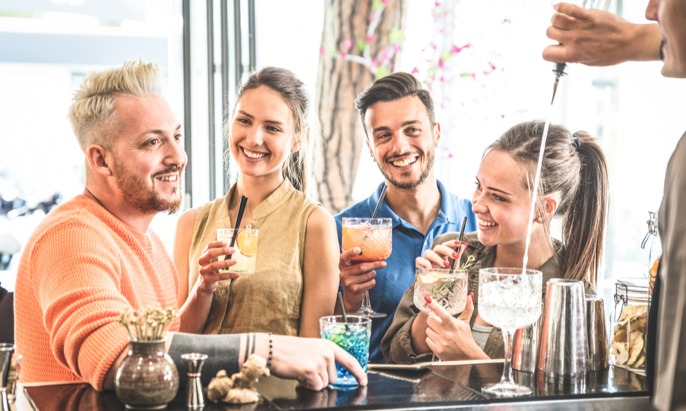 Group of friends drinking cocktails and talking at restaurant