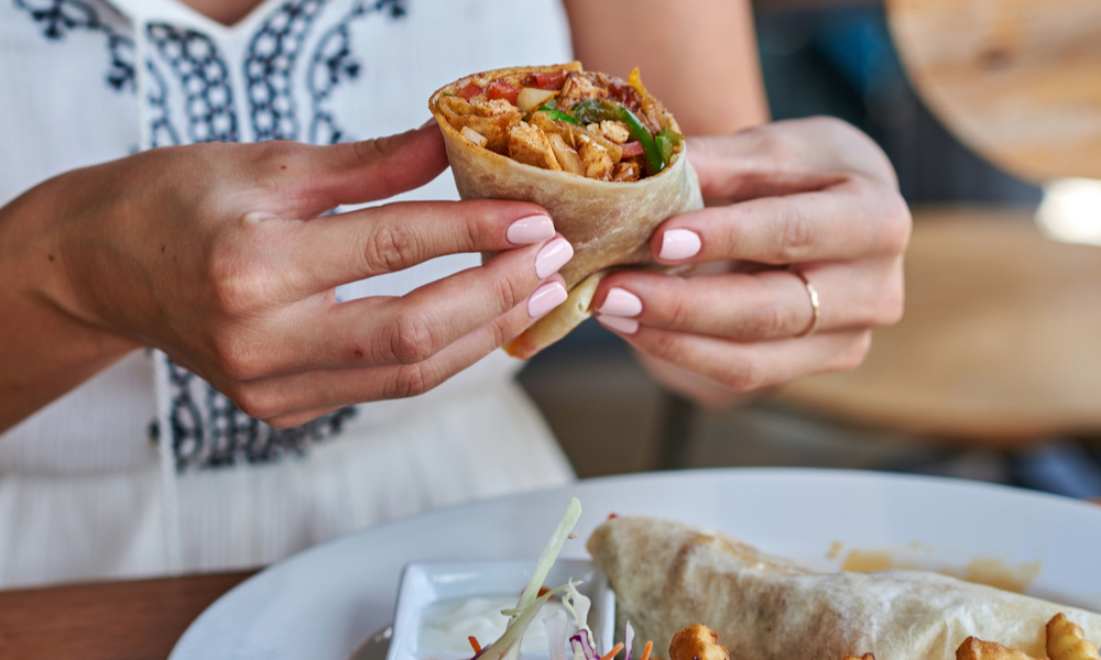Female hands holding tasty mexican burrito with different ingredients inside.