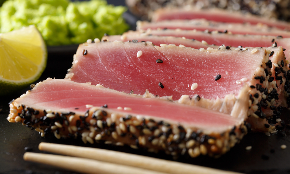 beautiful sliced tuna steak in sesame and wasabi, lime macro on the table. horizontal