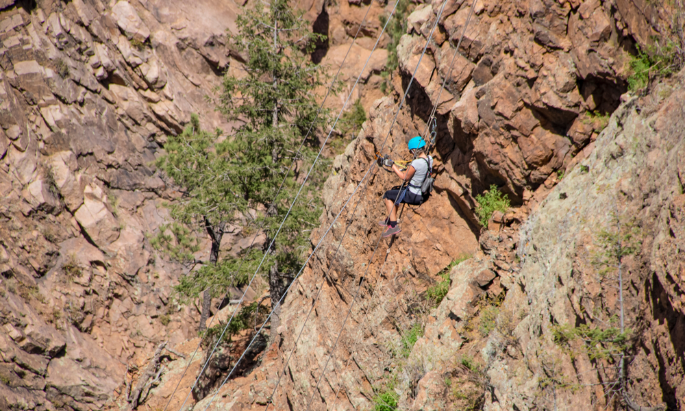 Exciting & adventurous things to do in denver: Woman ziplining down a cliff in the Rocky Mountains of Colorado