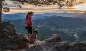 Exciting & adventurous things to do in denver: A hispanic woman is hiking with a dog, in the Rocky Mountains, of Colorado.